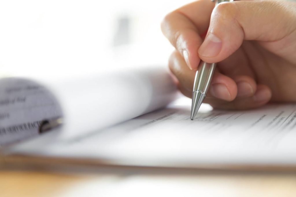 hand-writing-with-pen-completing-application-form
